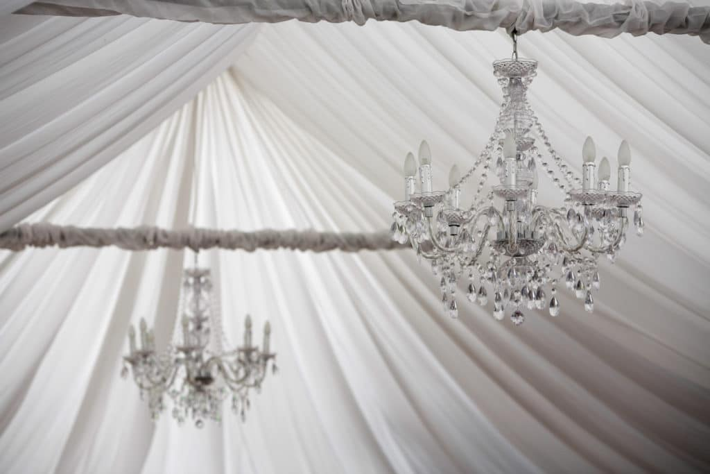 Chandelier with soft drapery at a wedding inside a tent or marquee