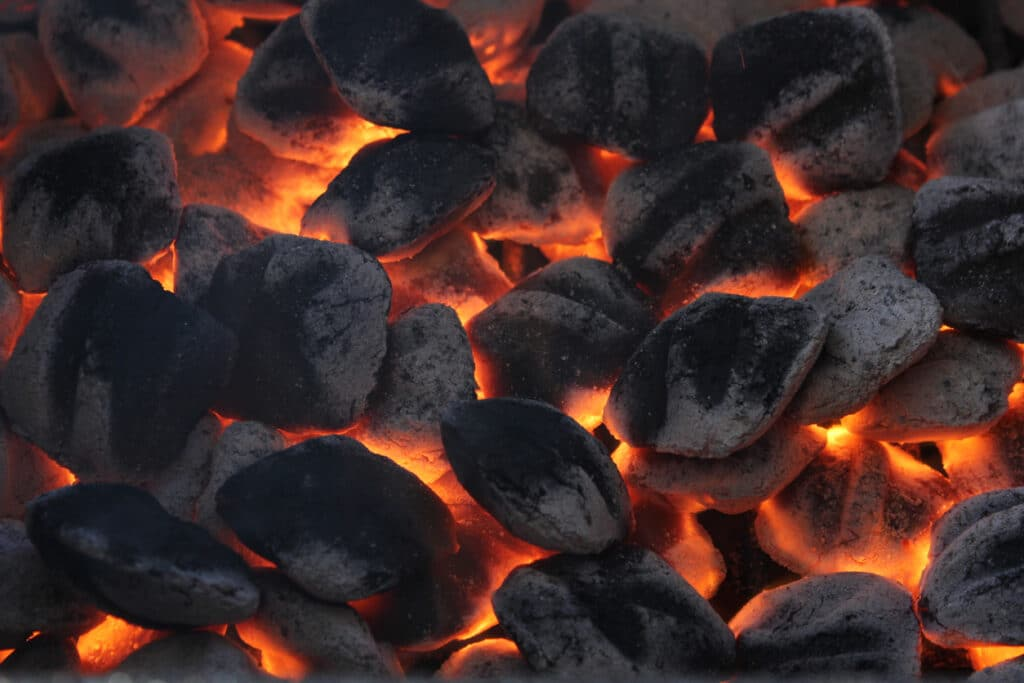 Many charcoal briquettes glowing in a barbecue