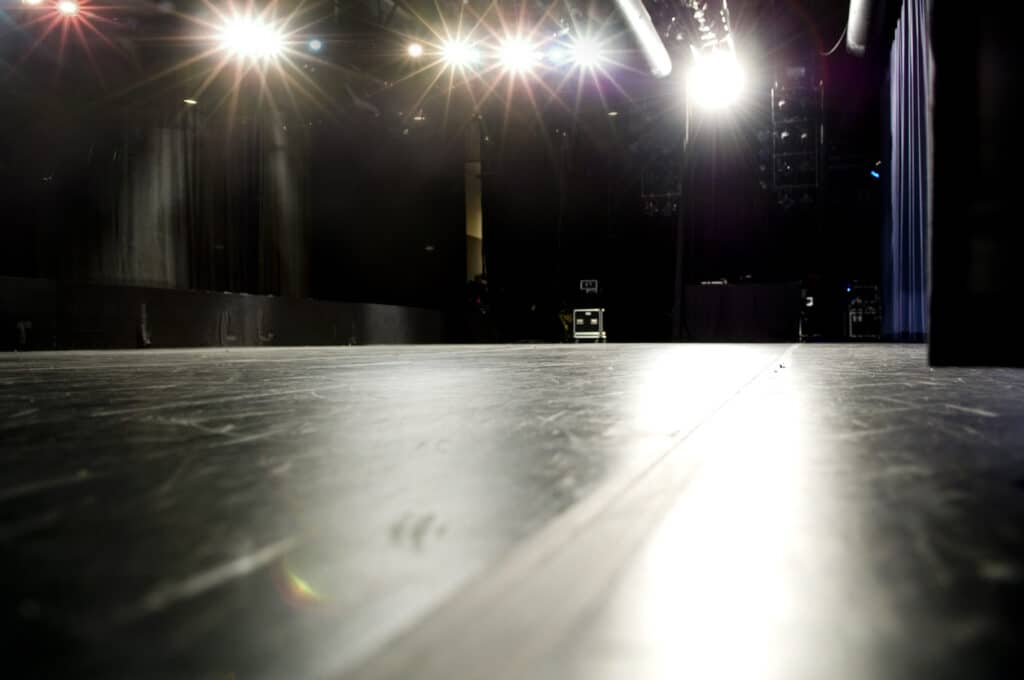 stage floor in production theater...focus is on center stage, shallow DOF...background noise visible.